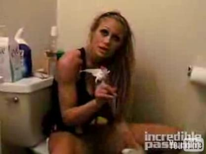 She takes out her tampon and holds it up to the camera.
